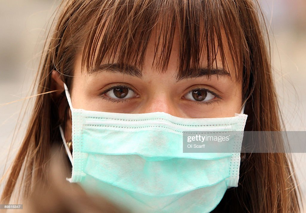 A woman wearing a surgical mask to prevent the transmission of airborne infection walks in Westminster on July 30 2009 in London England Figures...