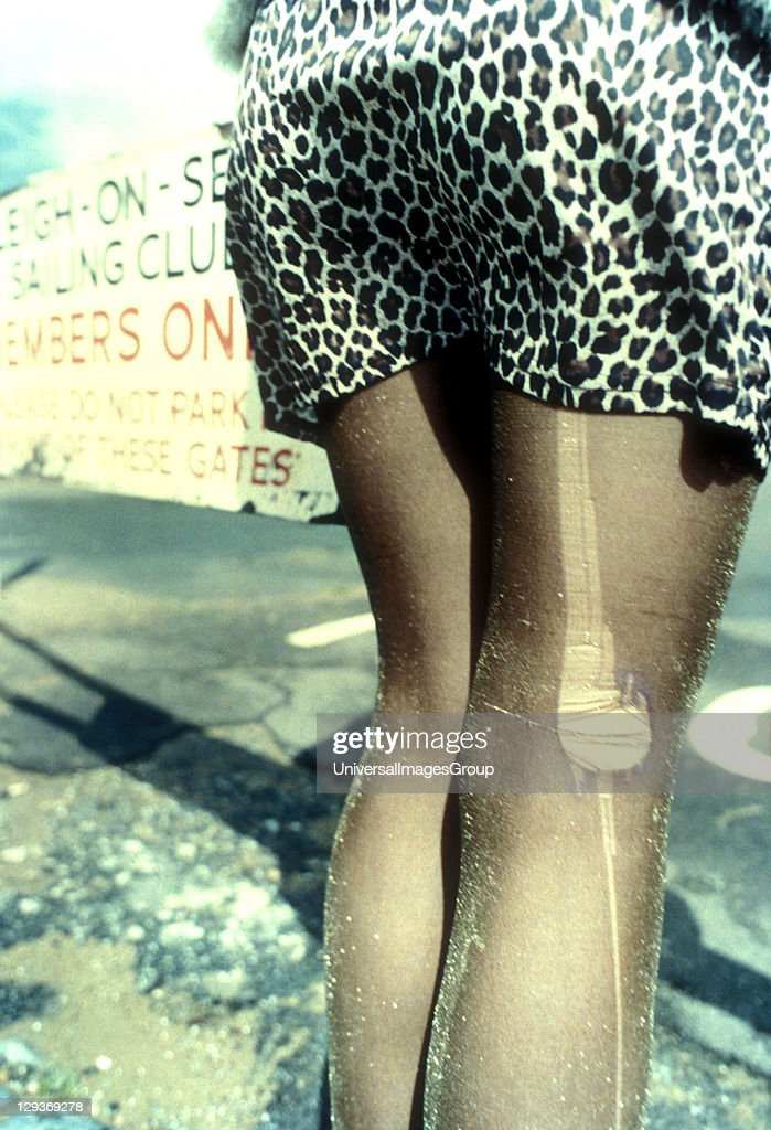 A woman wearing a tigerprint mini skirt with a hole in her tights