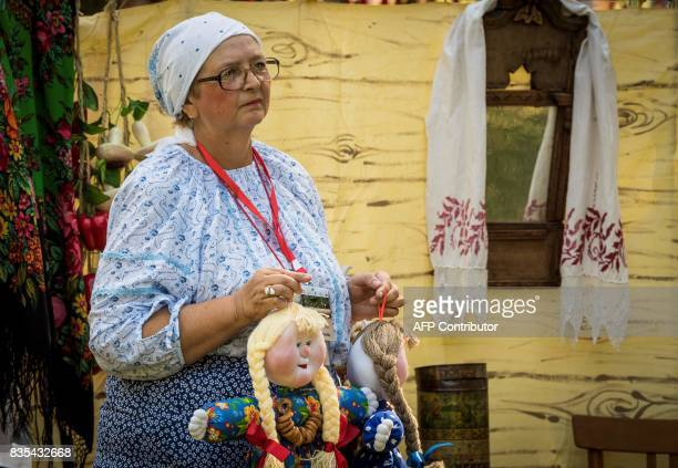 A woman wearing a traditional costume carries two dolls at a park in Yekaterinburg during a folk fest for the celebrations of the 294th anniversary...