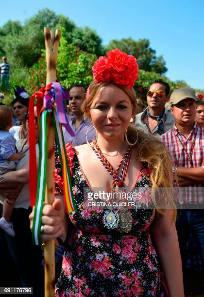 A woman wearing a traditional Rocio costume with necklaces of the Virgen del Rocio a stick with the colors of her brotherhood and a flower in her...