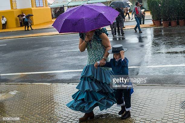 Woman wearing a traditional Sevillana dress holds an umbrella as she arrives with her son to the Feria de Abril under a heavy rain on April 12 2016...