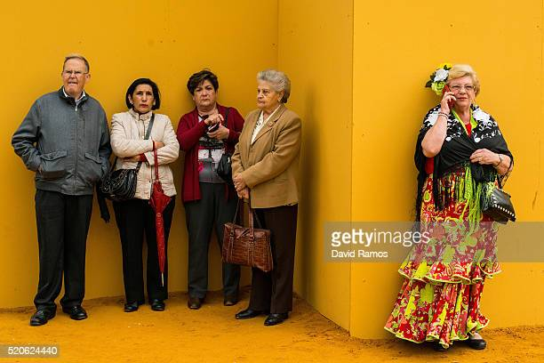 A woman wearing a traditional Sevillana dress speaks on her mobile phone next to visitors as they wait at the main entrance of the Feria de Abril...