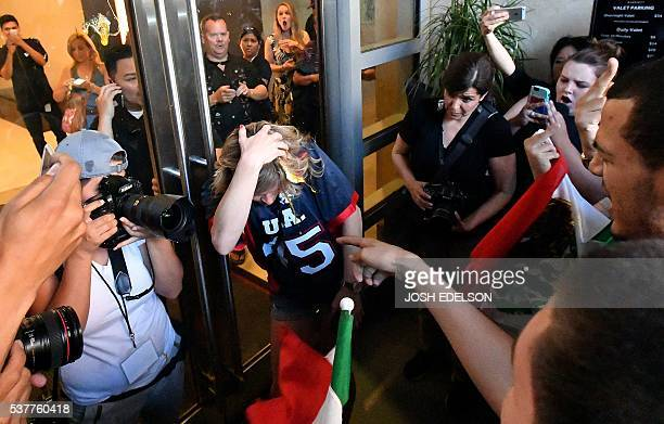 A woman wearing a Trump shirt is pelted with eggs by protesters while pinned against a door near where Republican presidential candidate Donald Trump...