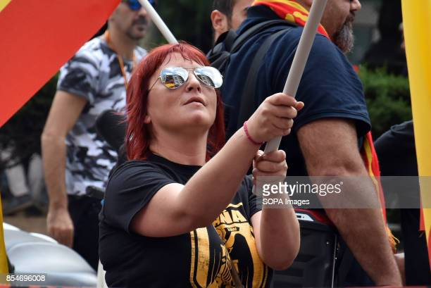 RàDIO BARCELONA CATALONIA SPAIN A woman wearing a tshirt with the emblem of the ultra right party is seen raising a flag of Spain during the protest...