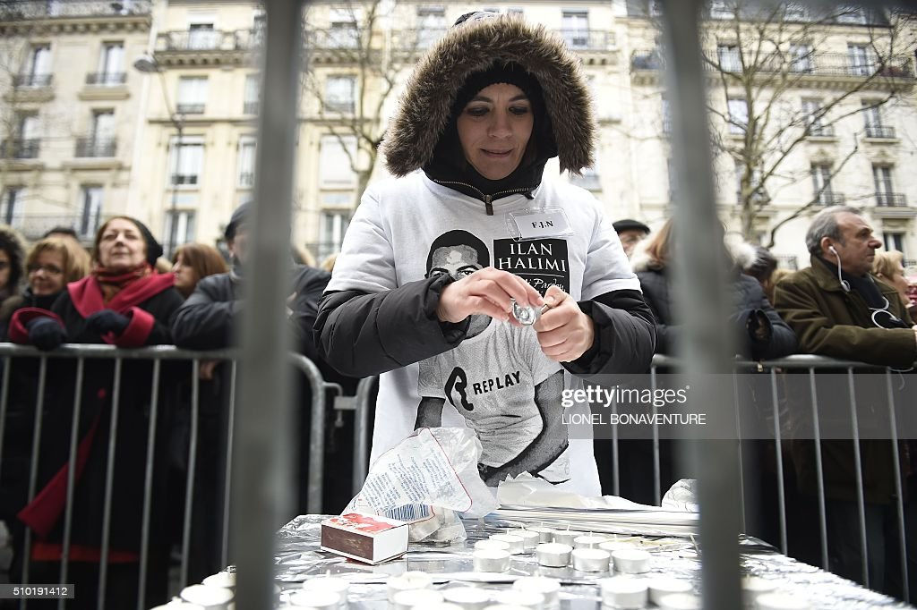 A woman wearing a t-shirt with the portrait of Ilan Halimi, lights a candle in front of the shop where Ilan was working, during a ceremony in tribute to him on February 14, 2016 in Paris, ten years after the 23-year-old Jewish Frenchman was murdered, on February 13, 2006 after he was kidnapped and tortured for three weeks by a gang in a Paris suburb. AFP PHOTO / LIONEL BONAVENTURE / AFP / LIONEL BONAVENTURE