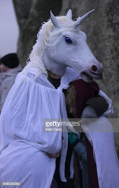 A woman wearing a unicorn mask shelters a girl as druids pagans and revellers gather hoping to see the sun rise as they take part in a winter...