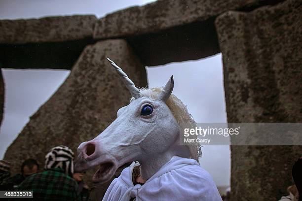 A woman wearing a unicorn mask watches as druids pagans and revellers gather hoping to see the sun rise as they take part in a winter solstice...