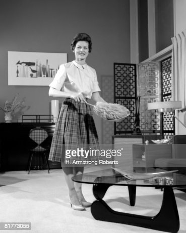 Woman Wearing A White Blouse & Plaid Skirt Dusting A Bowl With A Feather Duster In Front Of A Glass Top Coffee Table Smiling Modern Living Room. : Foto stock