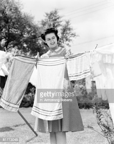 Woman Wearing A White Collar Poka Dot Cotton Dress Smiling While Pinning A Towel On A Clothes Line Clothes Prop Clothes Pin Foliage. : Stock Photo