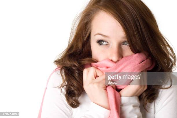 Woman wearing a white shirt covering her mouth with a scarf