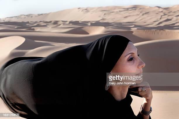 Woman wearing Abaya in desert, headshot.