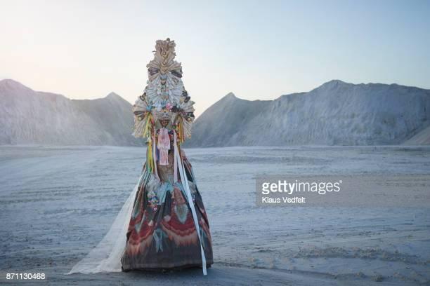 Woman wearing amazing costume, standing in limestone landscape