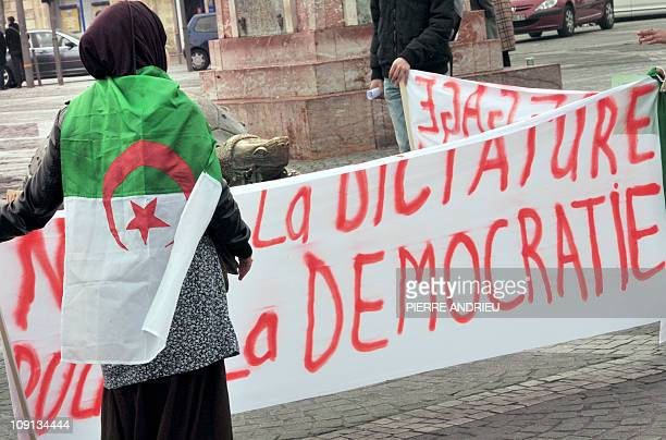 A woman wearing an Algerian flag holds a banner during a demonstration organized by French League of Human Rights in support to Egypt and Algeria on...
