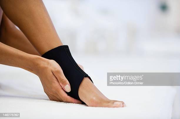 Woman wearing ankle brace, low section
