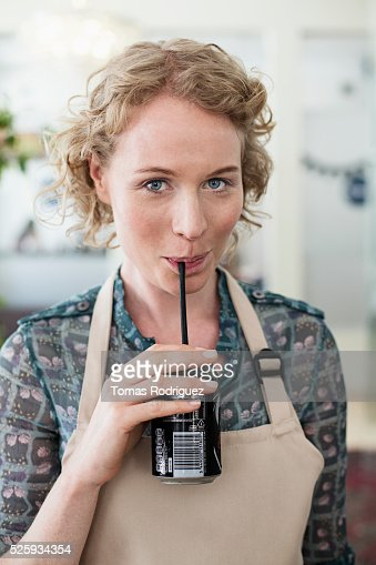Woman wearing apron drinking soda : Stockfoto