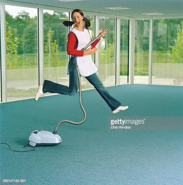 Woman wearing apron indoors, holding vacum cleaner, jumping in air
