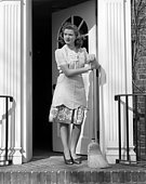 Woman Wearing Apron With Broom In Open Front Door Leaning On Broom Looking Unhappy Sad Sweep Clean Housewife.