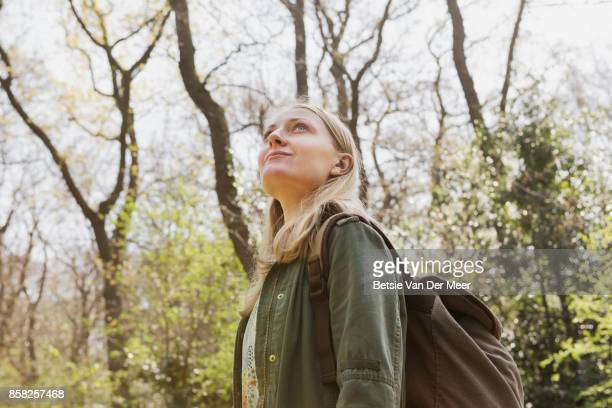 Woman wearing backpack looks at surroundings, walking in forest.