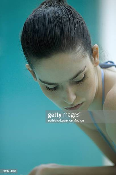 Woman wearing bathing suit, hair pulled back, looking down, close-up