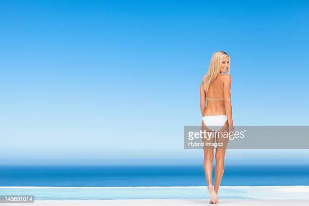 Woman wearing bikini by infinity pool