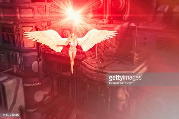 Woman wearing bikini flying with angel wings in industrial space