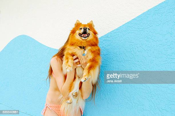Woman Wearing Bikini Hiding Behind Her Dog