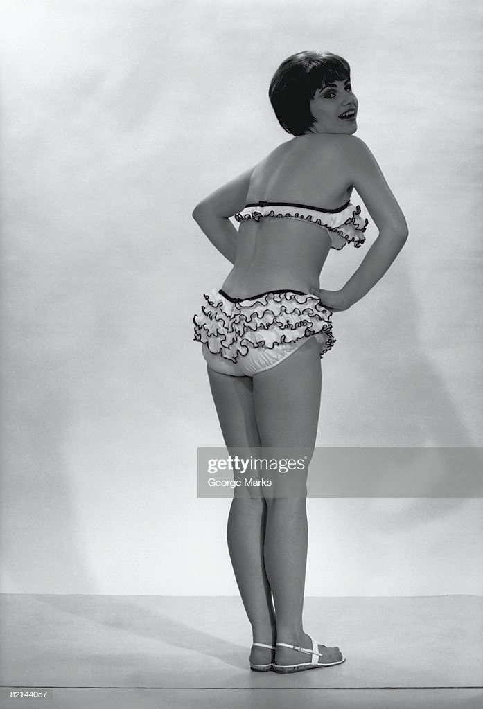 Woman wearing bikini posing in studio, (B&W), rear view : Stock Photo