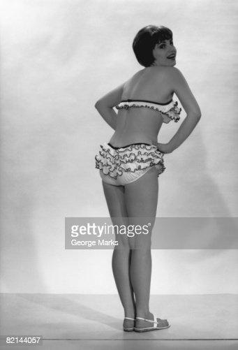 Woman wearing bikini posing in studio, (B&W), rear view : Stock Photo