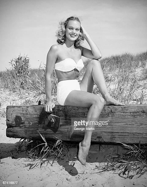 Woman wearing bikini sitting on log on beach, (B&W), (Portrait)