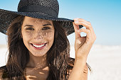Portrait of beautiful young woman wearing summer black hat with large brim at beach. Closeup face of attractive girl with black straw hat. Happy latin woman smiling and looking at camera with sea in b