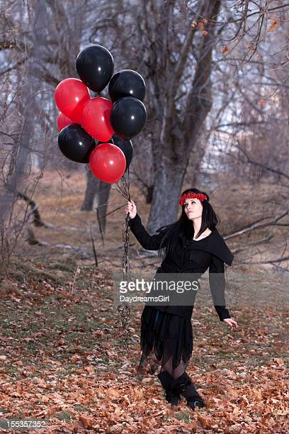 Woman Wearing Black Holding Balloons in Forest