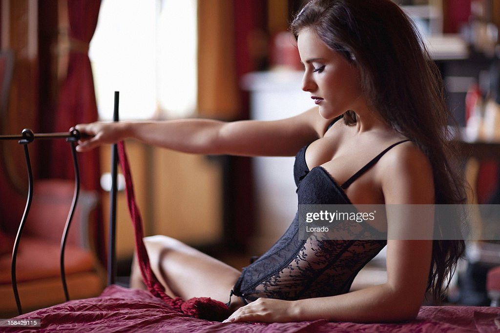 woman wearing black lingerie posing on bed : Stock Photo