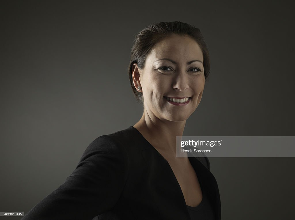 Woman wearing black on a dark background : Stock Photo