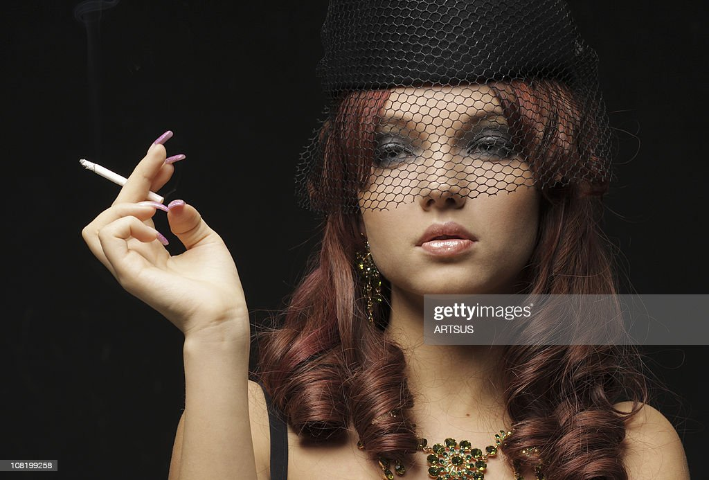http://media.gettyimages.com/photos/woman-wearing-black-veil-and-hat-smoking-picture-id108199258