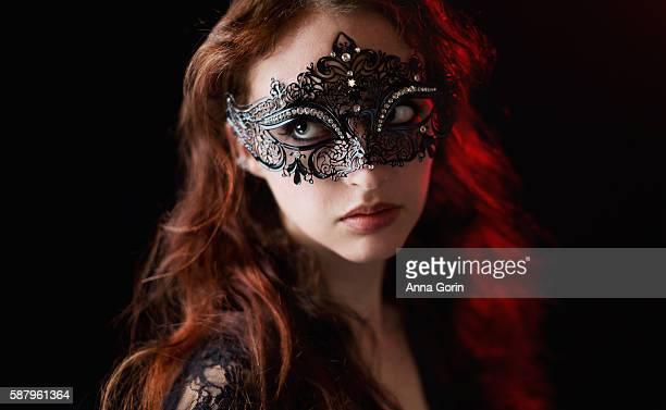 Woman wearing black Victorian masquerade mask looks away, black studio backdrop with low lighting