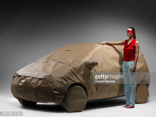 Woman wearing blindfold, hand on car wrapped in brown paper