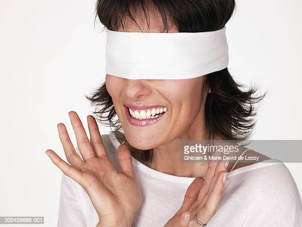 Woman wearing blindfold, smiling