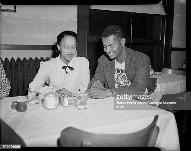 Woman wearing blouse with bow at neck and man wearing NAACP Youth Council tshirt and pinstriped jacket seated at table in restaurant or club...