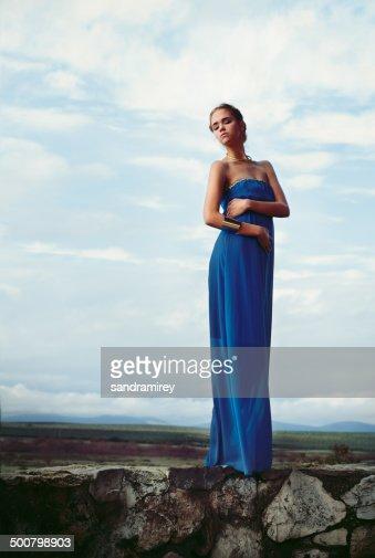 Woman wearing blue long dress standing on stone wall
