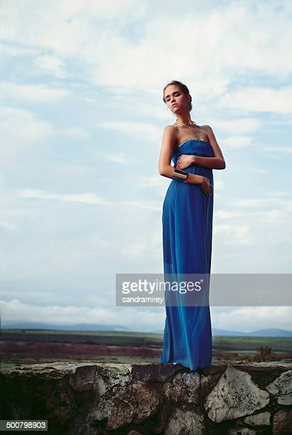 Woman wearing blue long dress standing on stone wall