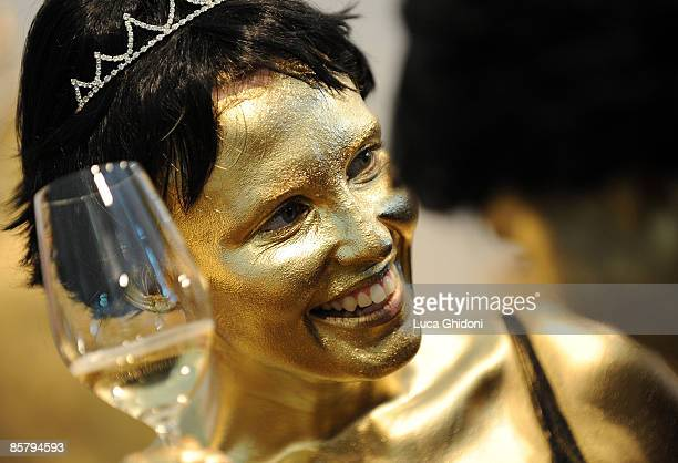 A woman wearing body paint poses with a glass of white wine at the Vinitaly on April 3 2009 in Verona Italy Vinitaly the international wine and...