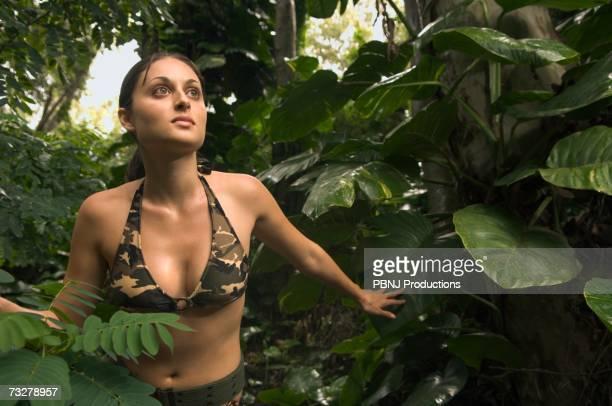 Woman wearing camouflage bikini in jungle
