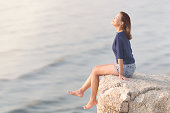 Side view portrait of Attractive fashion young Asian woman wearing casual sitting on the rock cliff relaxing, smiling and breathing deep fresh air with blurred sea wave ocean background.
