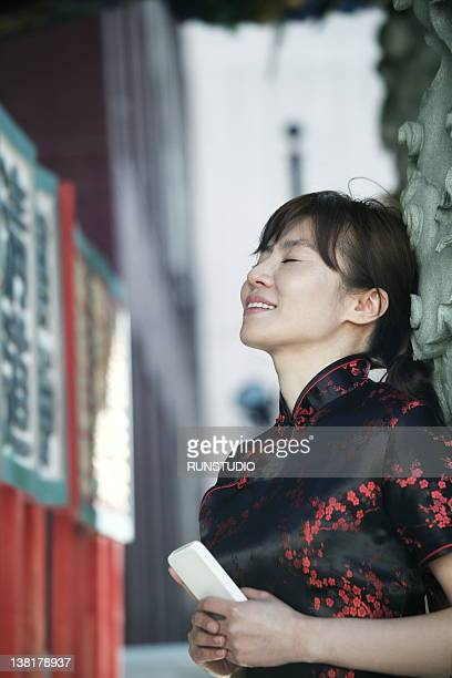 woman wearing china dress with a mobile phone