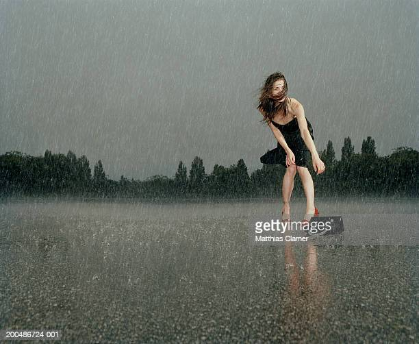 Woman wearing cocktail dress in rain, reaching for dropped purse