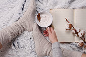 Woman wearing cozy warm wool socks, reading a book, drinking hot drink lose up. Warmth concept. Winter clothes
