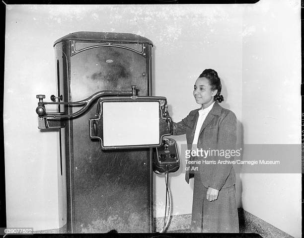 Woman wearing dark suit and light colored blouse with bow at neck standing beside Picker xray machine circa 19371946