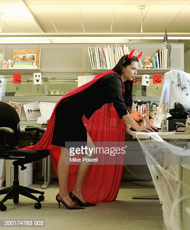Woman wearing devil costume working in cubicle decorated for Halloween : Stock Photo