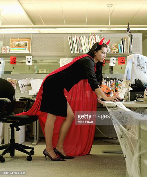 Woman wearing devil costume working in cubicle decorated for Halloween