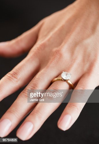 woman wearing diamond engagement ring close up stock photo